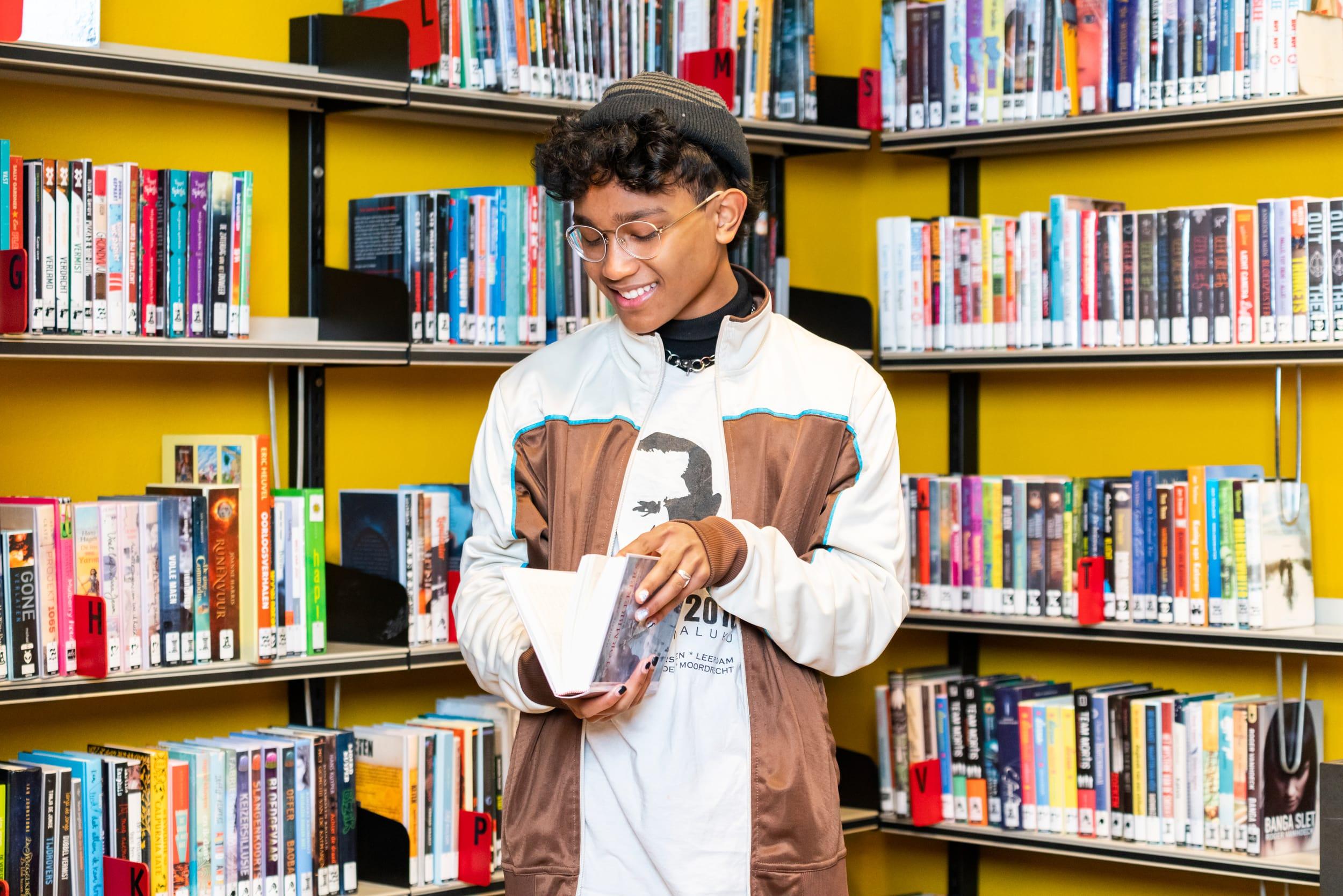 Jongen kiest een boek uit in de biebliotheek van Uithoorn