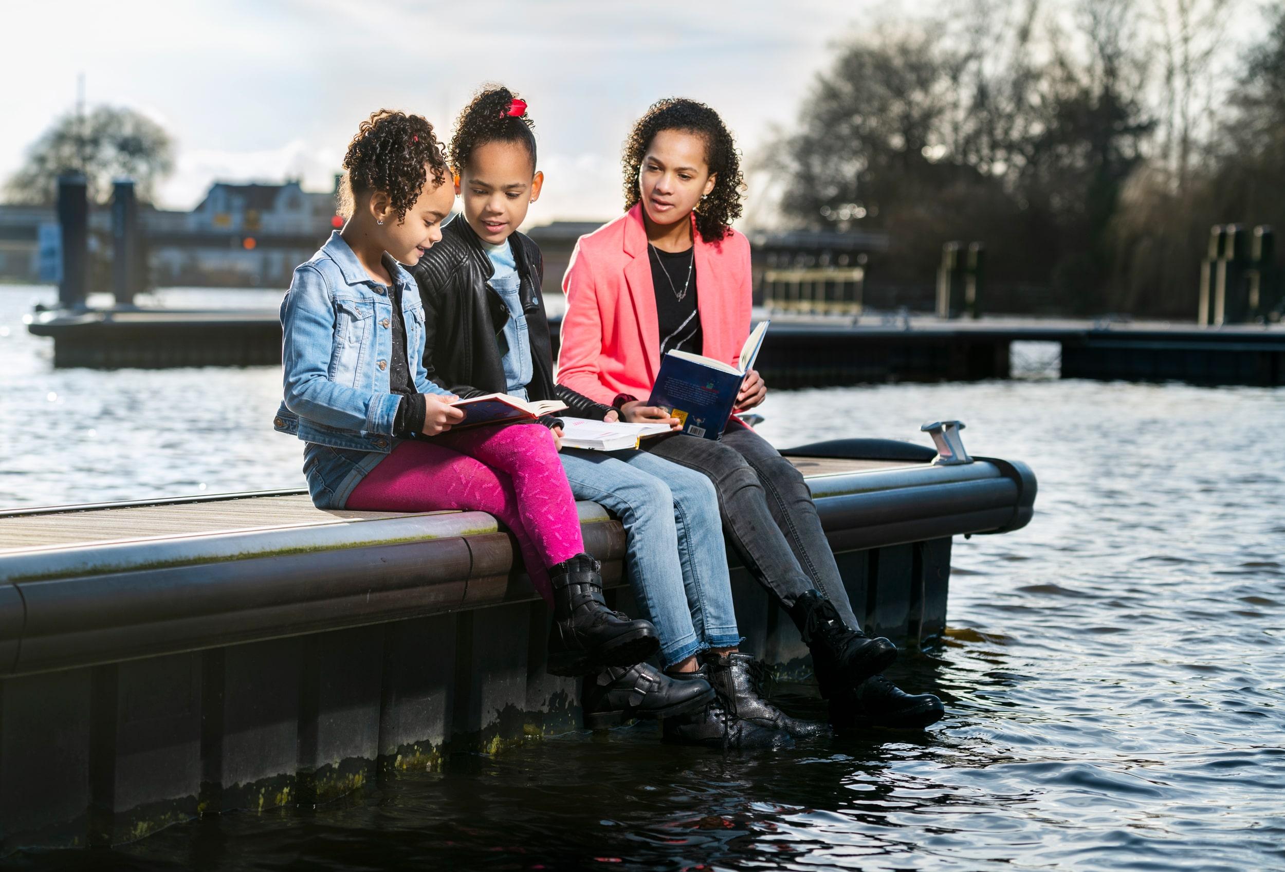 Kinderen lezen boeken in de haven van Uithoorn. Campagne fotografie voor de bibliotheek.