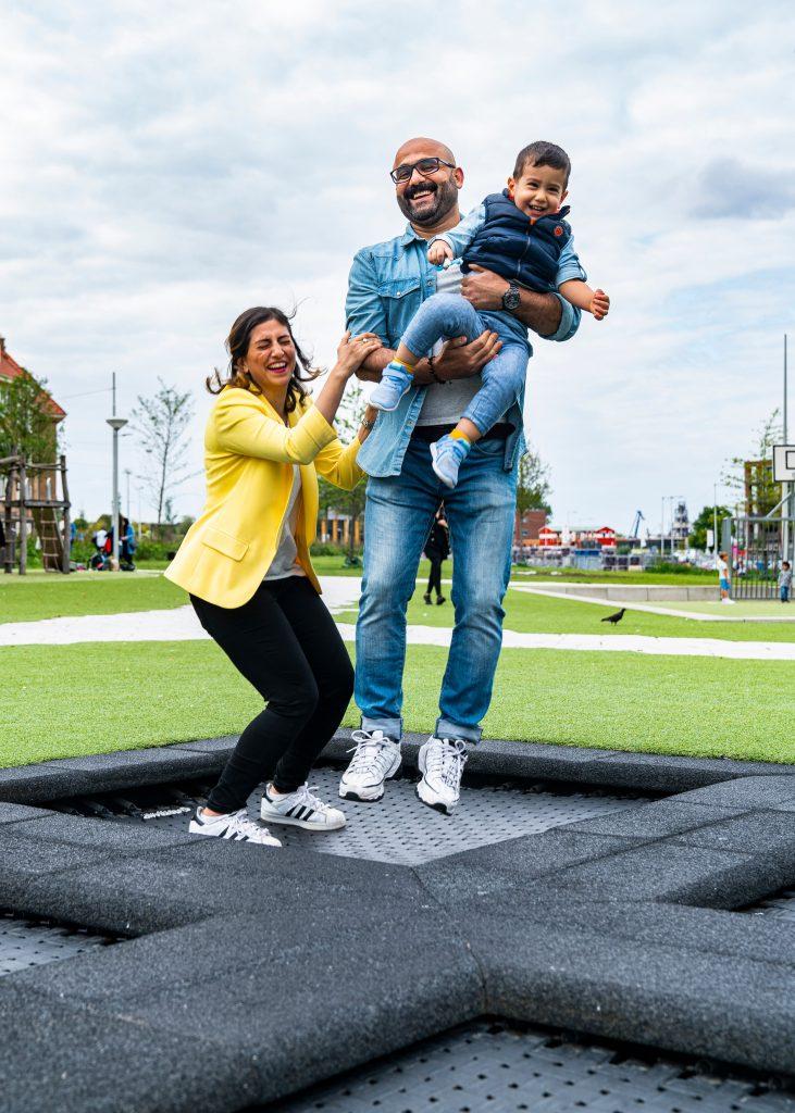 Portret van Familie Moradi. Spelend in de speeltuin van hun nieuwe woonbuurt.
