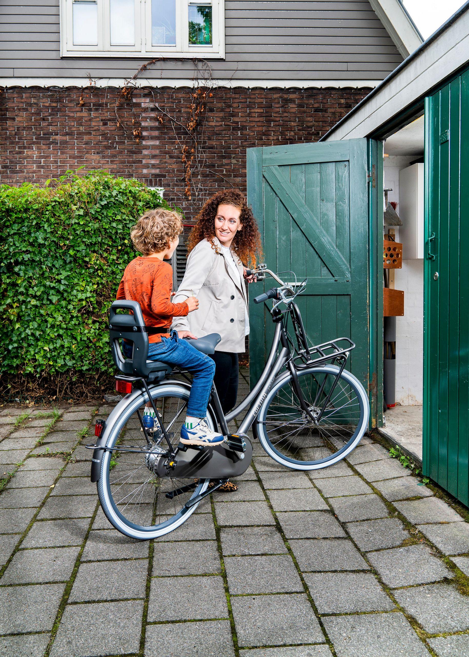 Moeder en zoon met fiets voor de schuur. Campagne fotografie voor Qibbel kinderfietszitjes.