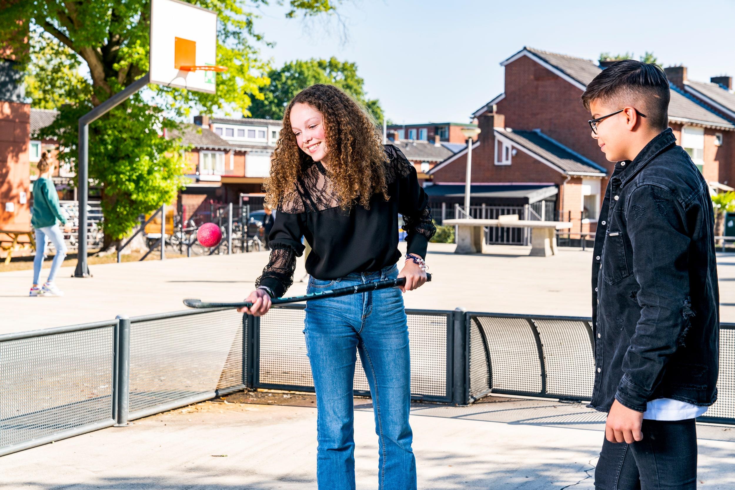 Scholieren spelen hockey op het schoolplein. Campagne fotografie voor Het stedelijk Lyceum Enschede.