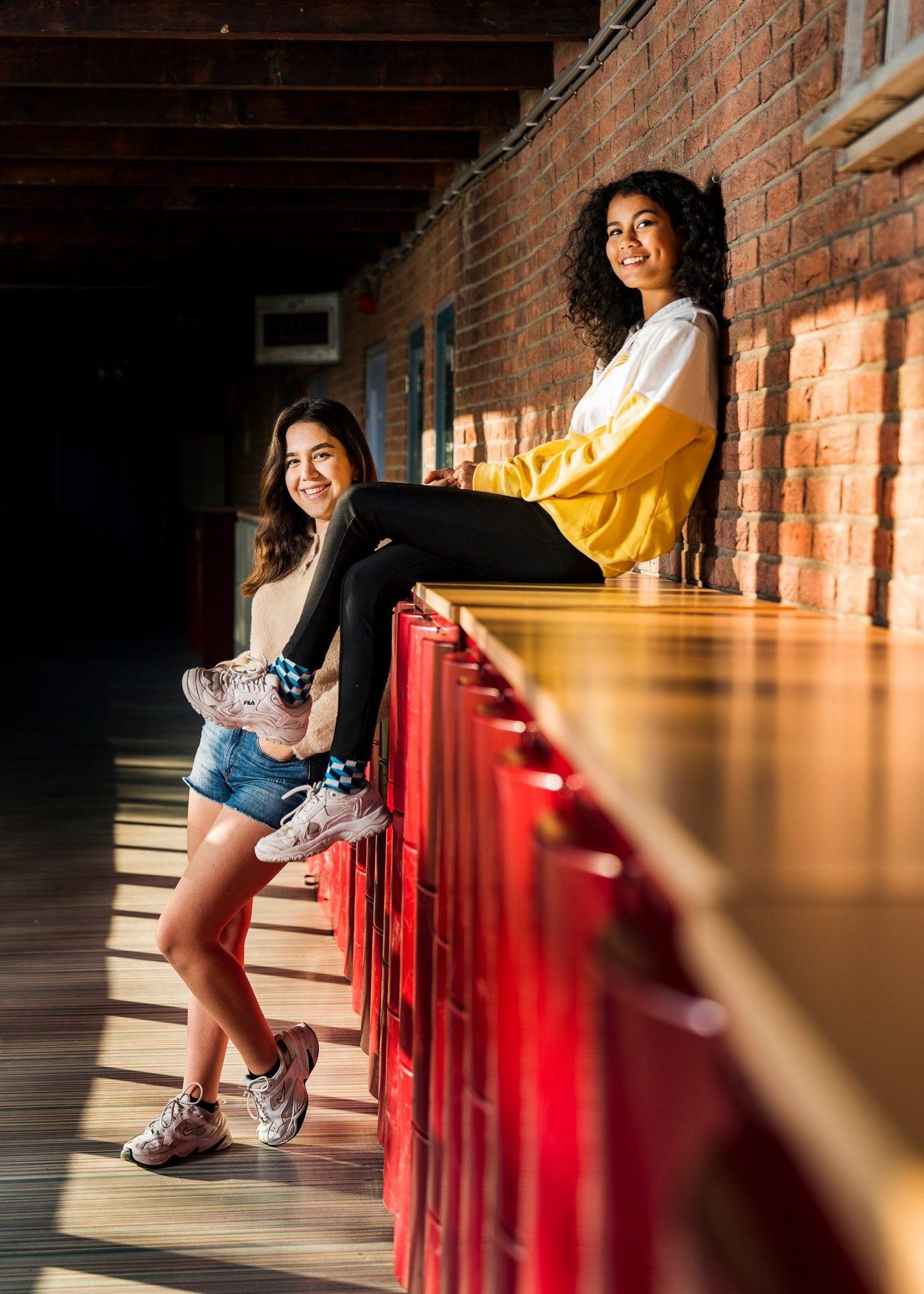 Leerlingen zitten bij de kluisjes op school. Campagne fotografe voor het Innova college.